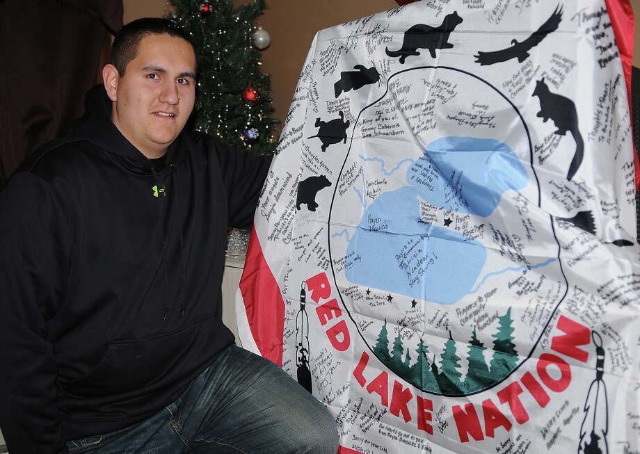 Justin Jourdain, a 2008 graduate of Red Lake High School who was  in the school during the shootings that occurred  in 2005, poses with a Red Lake Band of Chippewa flag signed by students and residents of the reservation in Bemidji, Minn. Jourdain and others are taking two signed flags on a trip to Newtown, Conn., to offer comfort to the grieving community in the wake of the tragic shootings at Sandy Hook Elementary School. Photo: AP