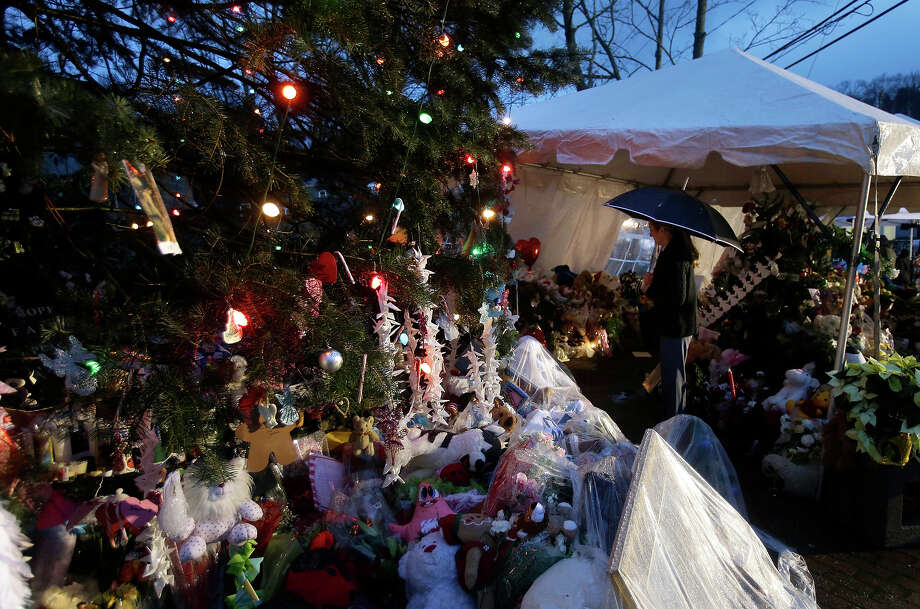 Kjirsten Meckert, who works in Hartford, Conn., visits a memorial to the Newtown shooting victims during a heavy down pour in the Sandy Hook village of Newtown, Conn., Friday, Dec. 21, 2012.  The shooter, Adam Lanza, walked into Sandy Hook Elementary School in Newtown, Dec. 14, and opened fire, killing 26 people, including 20 children, before killing himself.  Photo: AP