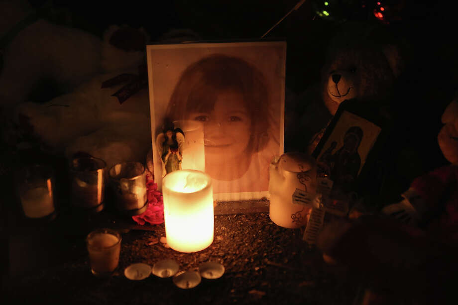 Candles and photos adorn a streetside memorial on December 20, 2012 in Newtown, Connecticut. Photo: John Moore, Getty Images / 2012 Getty Images