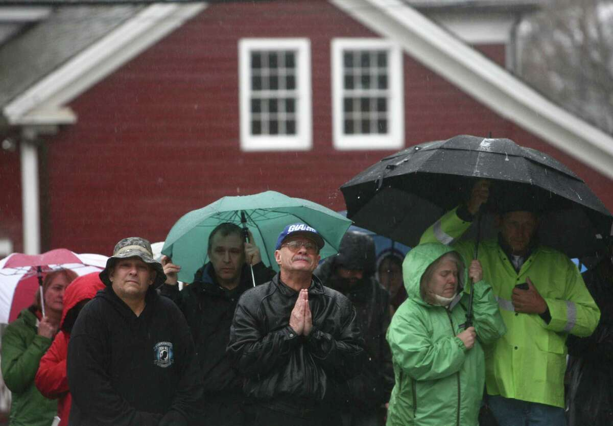 People, including Joe Saleem, center, observe a moment of silence led by Connecticut Governor Dannel Malloy, Lt. Governor Nancy Wyman and First Selectman Patricia Llodra in front of Edmond Town Hall in Newtown. The moment of silence and bell tolling was held across the state on Friday, December 21, 2012, the one week anniversary of the Sandy Hook shootings. Saleem said he lived in Newtown for 54 years but moved to North Carolina. But after the violence that took 28 people, Saleem returned to his hometown.
