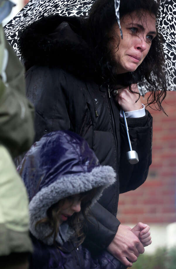 Sarah Baroody holds her daughter Sophia's hand and cries while observing a moment of silence as bells rang 26 times in Newtown, Conn., Friday, Dec. 21, 2012. The chiming of bells reverberated throughout Newtown, commemorating one week since the crackle of gunfire in a schoolhouse killed 20 children and six adults in a massacre that has shaken the community and the nation. Photo: AP