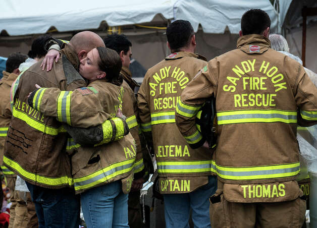 Members of the Sandy Hook Volunteer Fire and Rescue department hug after a moment of silence in Sandy Hook village on December 21, 2012 in Newtown, Connecticut. People around the United States joined in a moment of silence at 9:30 am to mark the one week anniversary of the Sandy Hook Elementary School shootings, while bells also rang 26 times to honor the victims of alleged gunman Adam Lanza, not including his mother Nancy Lanza who was killed at their family home. Photo: BRENDAN SMIALOWSKI, AFP/Getty Images / 2012 AFP