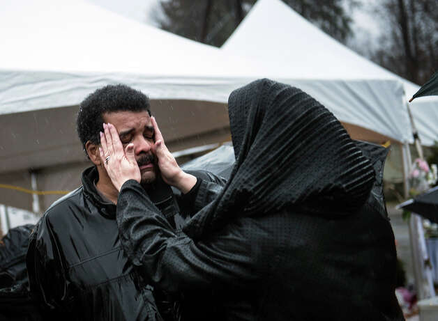 A woman wipes the face of a man after a moment of silence in Sandy Hook village December 21, 2012 in Newtown, Connecticut. People around the United States joined in a moment of silence at 9:30 ET am to mark the one week anniversary of the Sandy Hook Elementary School shootings while bells also rang 26 times to honor the victims of alleged gunman Adam Lanza, not including his mother Nancy Lanza who was killed at their family home. Photo: BRENDAN SMIALOWSKI, AFP/Getty Images / 2012 AFP