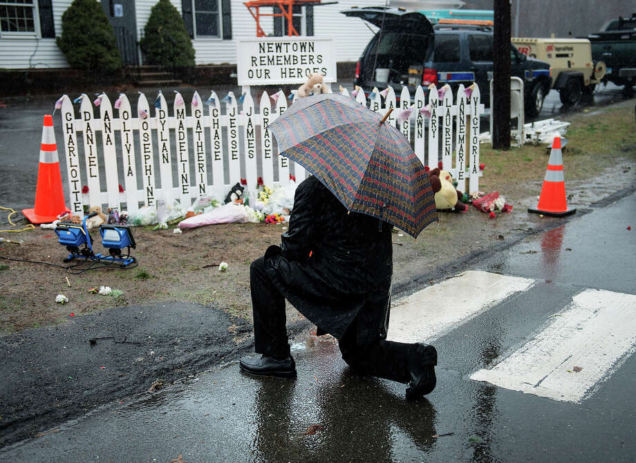A man kneels at a picket fence with the names of shooting victims during a moment of silence in Sandy Hook village and December 21, 2012 in Newtown, Connecticut. People around the United States joined in a moment of silence at 9:30 am to mark the one week anniversary of the Sandy Hook Elementary School shootings, while bells also rang 26 times to honor the victims of alleged gunman Adam Lanza, not including his mother Nancy Lanza who was killed at their family home.  AFP PHOTO/Brendan SMIALOWSKI Photo: BRENDAN SMIALOWSKI, AFP/Getty Images / 2012 AFP