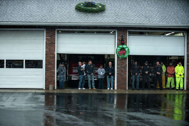 Members of the Sandy Hook Volunteer Fire and Rescue department stand during moment of silence in Sandy Hook village December 21, 2012 in Newtown, Connecticut. People around the United States joined in a moment of silence at 9:30 am ET to mark the one week anniversary of the Sandy Hook Elementary School shootings while bells also rang 26 times to honor the victims of alleged gunman Adam Lanza, not including his mother Nancy Lanza who was killed at their family home.  AFP PHOTO/Brendan SMIALOWSKI Photo: BRENDAN SMIALOWSKI, AFP/Getty Images / 2012 AFP