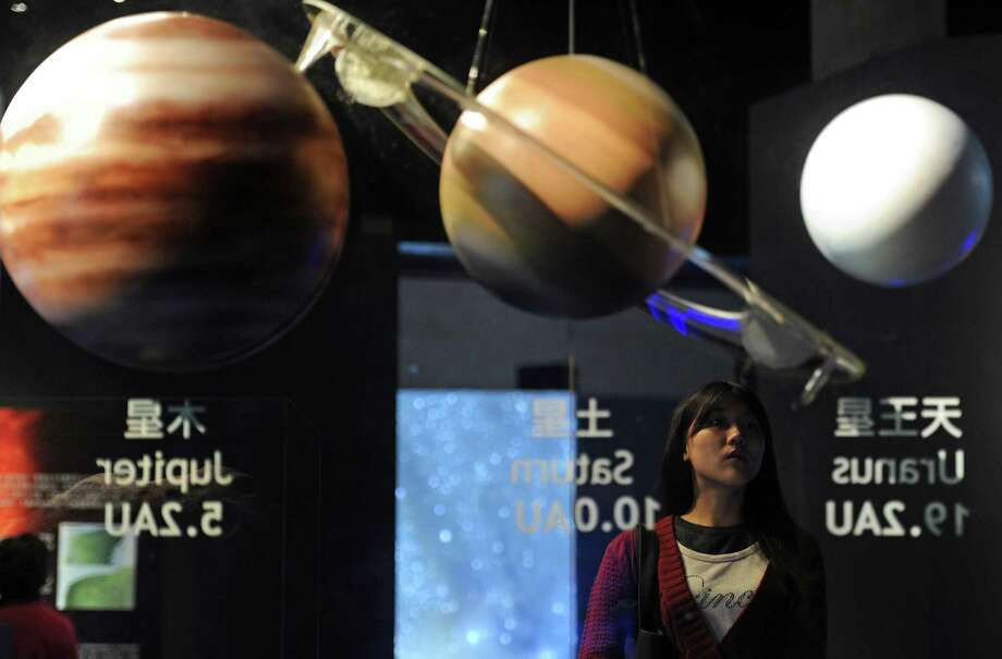 A young woman looks at models of the planets at the National Museum of Natural Science in central Taichung on Friday. The display was supposed to be reassuring. (Photo credit should read SAM YEH/AFP/Getty Images) Photo: SAM YEH, Ap/getty / 2012 AFP