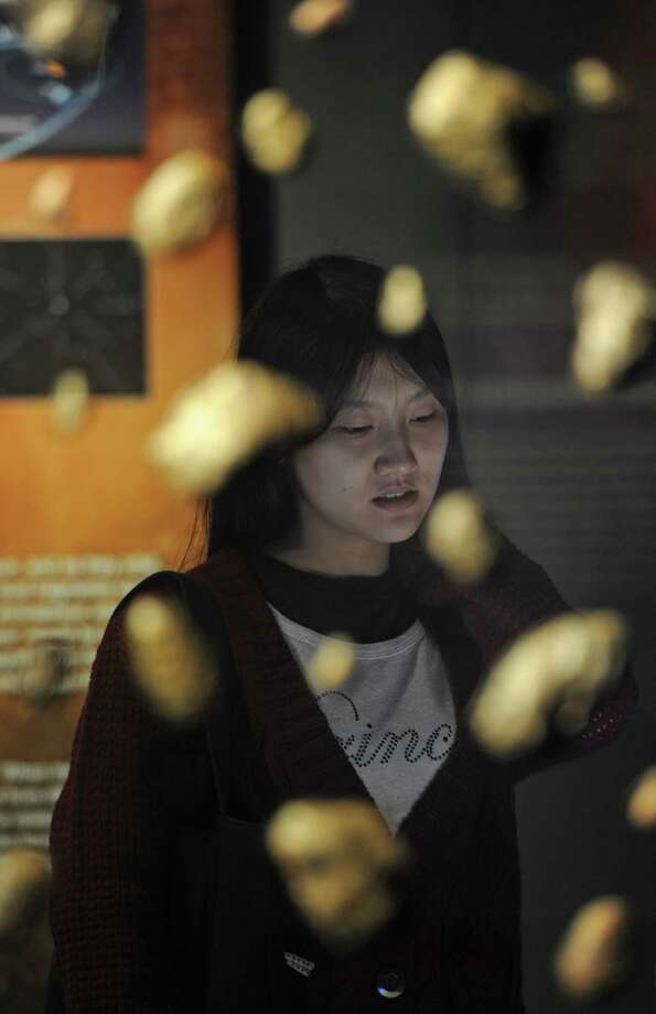 At the National Museum of Natural Science in Taichung, Taiwan, there was a ceremony to assure people the world wasn't ending. Here a woman looks at a display about meteorites and perhaps hoping the Big One stays away. (SAM YEH/AFP/Getty Images) Photo: Ap/getty