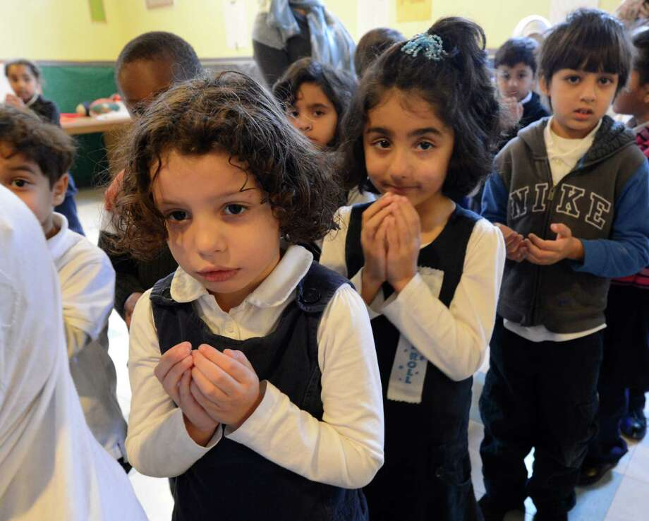 Second grade students Suhailah Elgewili, left and Farhana Hassan, center  observe a moment of silence Friday morning, Dec 21, 2012, at the Annur Islamic School in Colonie, N.Y. in memory of the 20 children and six teachers who perished at the Sandy Hook Elementary School in Newtown, Conn. one week ago.  (Skip Dickstein/Times Union) Photo: SKIP DICKSTEIN