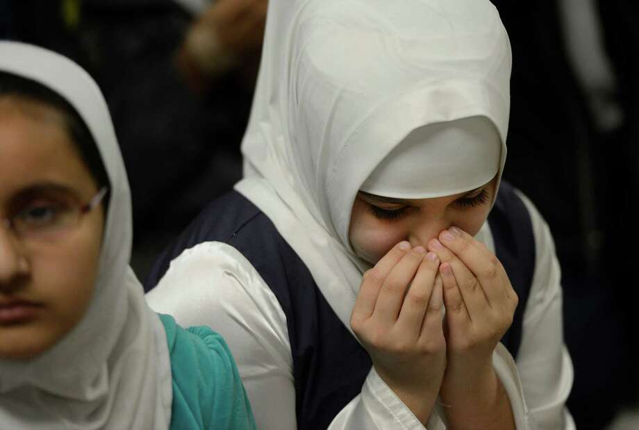 Fourth grader Husna Majid, who lost her father to a terrorist attack in Afghanistan on June 12, observes a moment of silence Friday Dec. 21, 2012, at the Annur Islamic School in Colonie, N.Y. in memory of the 20 children and six teachers who were gunned down at Sandy Hook Elementary School in Newtown, Conn. one week ago. (Skip Dickstein/Times Union) Photo: SKIP DICKSTEIN
