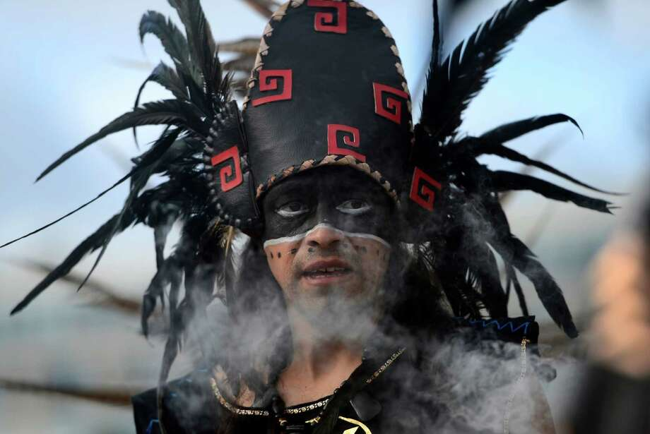 The Spanish have a lock on celebrations from running with the bulls to the world's biggest tomato fight. In Madrid on Friday, a dancer dressed in a costume and a head-dress performed during a ceremony marking the end of the Mayan age. (PIERRE-PHILIPPE MARCOU,PIERRE-PHILIPPE MARCOU/AFP/Getty Images) Photo: AFP, Ap/getty / 2012 AFP