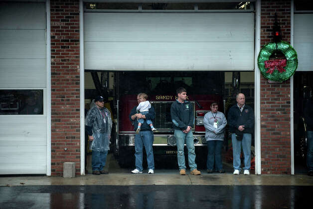 Members of the Sandy Hook Volunteer Fire and Rescue department stand during a moment of silence in Sandy Hook village December 21, 2012 in Newtown, Connecticut. People around the United States joined in a moment of silence at 9:30 am ET to mark the one week anniversary of the Sandy Hook Elementary School shootings while bells also rang 26 times to honor the victims of alleged gunman Adam Lanza, not including his mother Nancy Lanza who was killed at their family home.  AFP PHOTO/Brendan SMIALOWSKI Photo: BRENDAN SMIALOWSKI, AFP/Getty Images / 2012 AFP