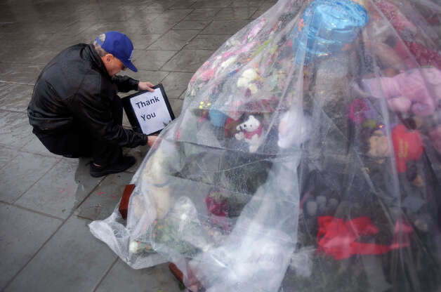 Joe Saleem of North Carolina tries to keep a memorial to the Newtown shooting victims dry under plastic on a rainy day in Newtown, Conn., Friday, Dec. 21, 2012.  The chiming of bells reverberated throughout Newtown, commemorating one week since the crackle of gunfire in a schoolhouse killed 20 children and six adults in a massacre that has shaken the community and the nation. Photo: AP