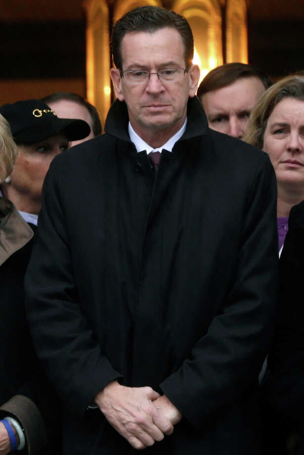 Connecticut Governor Dan Malloy stands with other officials to observe a moment of silence while bells ring 26 times in Newtown, Conn., Friday, Dec. 21, 2012. The chiming of bells reverberated throughout Newtown, commemorating one week since the crackle of gunfire in a schoolhouse killed 20 children and six adults in a massacre that has shaken the community and the nation. Photo: AP