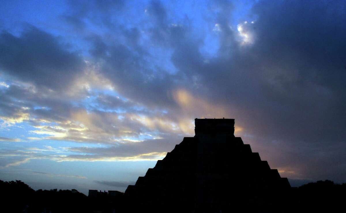 Cue the spooky music as the sun rises behind the Kukulkan temple in Chichen Itza, Mexico, on Friday. The last day on Earth!. Nah, the folks who gathered her burned ceremonial fires and blew conches to greet the dawn and the end of a vast, 5,125-year cycle in the Mayan calendar. The hundreds gathered in the ancient Mayan city said they believed it marked the birth of a new and better age. (AP Photo/Israel Leal)