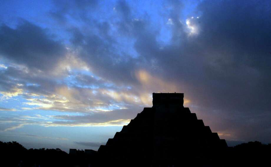 Cue the spooky music as the sun rises behind the Kukulkan temple in Chichen Itza, Mexico, on Friday. The last day on Earth!. Nah, the folks who gathered her burned ceremonial fires and blew conches to greet the dawn and the end of a vast, 5,125-year cycle in the Mayan calendar. The hundreds gathered in the ancient Mayan city said they believed it marked the birth of a new and better age. (AP Photo/Israel Leal) Photo: Ap/getty