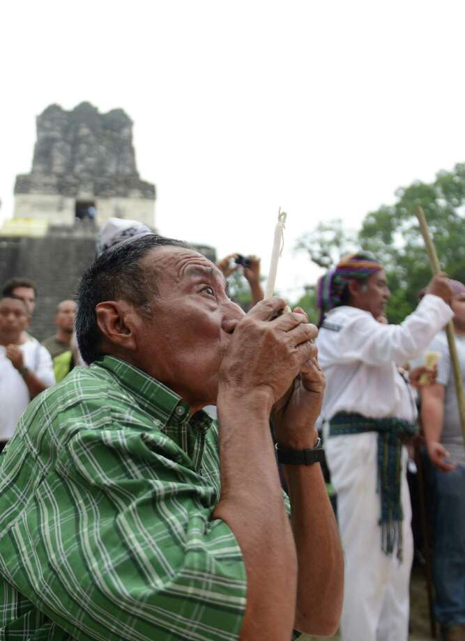 A man kisses a bunch of candles for an offering during in a ceremony on Friday celebrating the end of the Mayan cycle known as Bak'tun 13 and the start of the Maya new age, at the Tikal archaeological site, north of Guatemala City. (JOHAN ORDONEZ/AFP/Getty Images) Photo: JOHAN ORDONEZ, Ap/getty / 2012 AFP