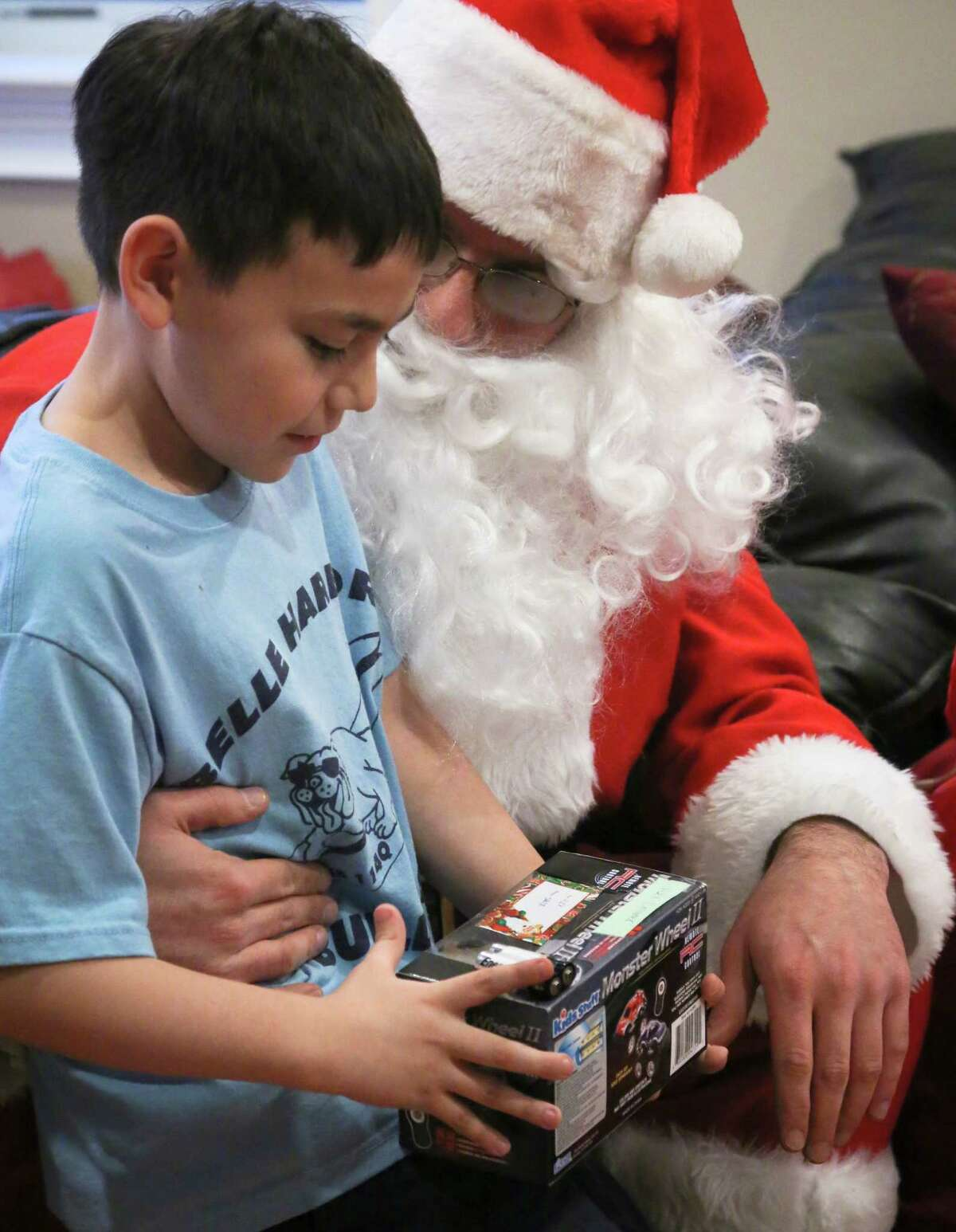 In this Tuesday, Dec. 18, 2012 photo, Alex Creamer, 9, receives a toy from Michael Sciaraffo, as Santa Claus, in the Belle Harbor neighborhood of the Queens borough of New York. Using Facebook, Sciaraffo started a charitable enterprise to collect and personally deliver toys to children affected by Superstorm Sandy, dressed as Santa Claus.