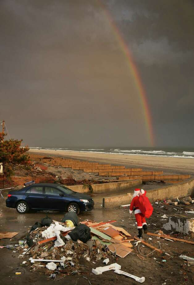 In this Tuesday, Dec. 18, 2012 photo, a rainbow appears as a Santa-dressed Michael Sciaraffo leaves the home of Ella Sampol, 14 months, after bringing her a toy in the Belle Harbor neighborhood of the Queens borough of New York. Using Facebook, Sciaraffo started a charitable enterprise to collect and personally deliver toys to children affected by Superstorm Sandy, dressed as Santa Claus. Photo: Bebeto Matthews, AP / AP