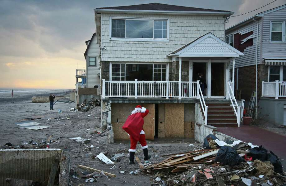 In this Tuesday, Dec. 18, 2012 photo, Michael Sciaraffo, a political consultant who has worked for Hillary Clinton and City Hall,  is costumed as Santa Claus as he makes a toy delivery to a home in the Bell Harbor neighborhood of New York with a delivery of toys. Using Facebook, Sciaraffo started a charitable enterprise to collect and personally deliver toys to children affected by Superstorm Sandy, dressed as Santa Claus. Photo: Bebeto Matthews, AP / AP