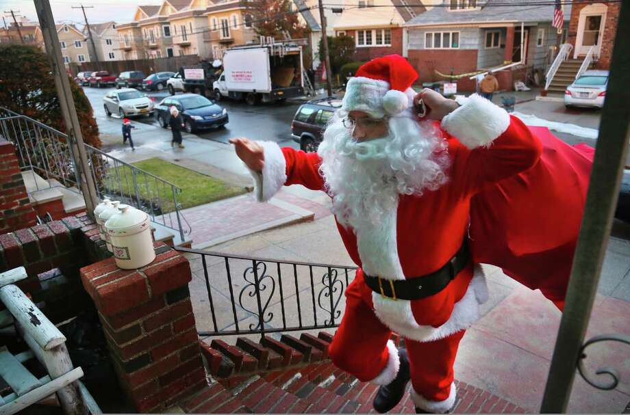 In this Tuesday, Dec. 18, 2012 photo, Michael Sciaraffo, as Santa Claus, arrives at the home of the Creamer family to deliver toys  in the Belle Harbor neighborhood of the Queens borough of New York. Using Facebook, Sciaraffo started a charitable enterprise to collect and personally deliver toys to children affected by superstorm Sandy, dressed as Santa Claus. Photo: Bebeto Matthews, AP / AP