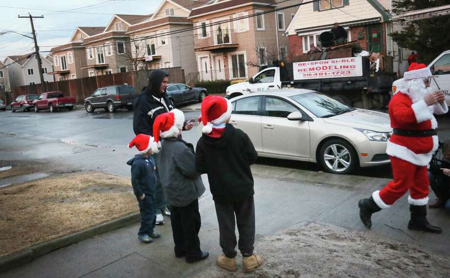 In this Tuesday, Dec. 18, 2012 photo, John Taylor, far left, his sons Nicholas, 5, second from left, and Johnny, 9,  second from right, and their neighbor Liam Siederman, 10, center, watch as Michael Sciaraffo, as Santa Claus, leaves with a promise getting them toys  in the Belle Harbor neighborhood of the Queens borough of New York. Using Facebook, Sciaraffo started a charitable enterprise to collect and personally deliver toys to children affected by Superstorm Sandy, dressed as Santa Claus. Photo: Bebeto Matthews, AP / AP