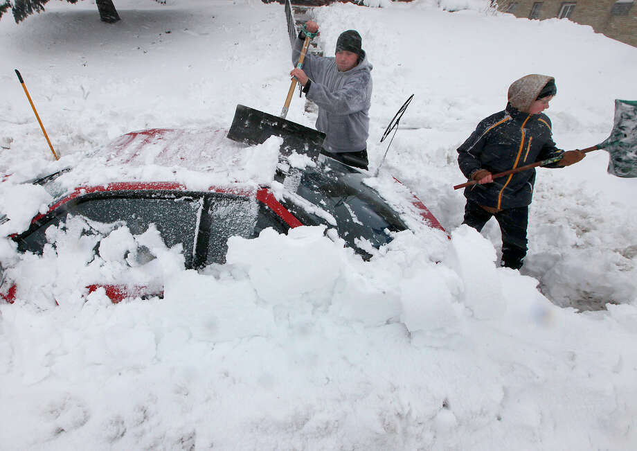 Luke McHenry, left, his son, Sebastian Wells, dig out their snow-buried vehicle as residents in Madison, Wis. contend with a severe winter storm that moved through the upper Midwest Thursday, December 20, 2012. Photo: John Hart, AP / Wisconsin State Journal