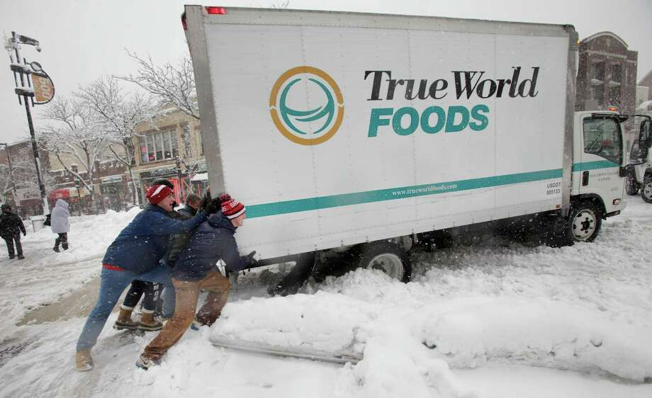 A group of University of Wisconsin-Madison students assist a food delivery truck driver in freeing his truck after making a stop at Wasabi Japanese Restaurant on State Street in Madison, Wis., Thursday afternoon, Dec. 20, 2012. They were not successful. Photo: Michael P. King, AP / Wisconsin State Journal