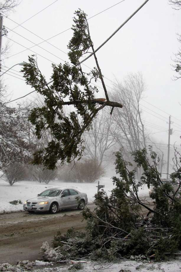 Cars pass under a branch from a fallen pine tree that dangles on a power line across West Ave. at the intersection of Morningside Dr. during the snowstorm Thursday Dec. 20, 2012 in Burlington, Iowa. The weather changed from rain to high winds causing white out conditions. Photo: JOHN GAINES, AP / THE HAWK EYE