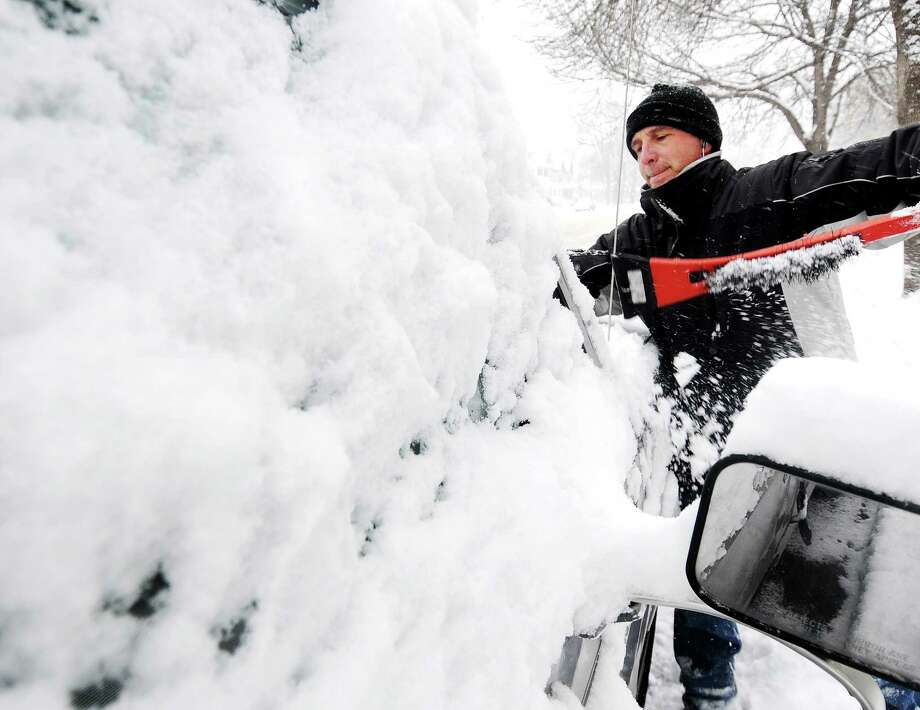Joe Jackson clears off snow from his truck on Thursday, Dec. 20, 2012, in Winona, Minn.  The first major snowstorm of the season began its slow eastward march across the Midwest early Thursday, creating treacherous driving conditions and threatening to disrupt some of the nation's busiest airports ahead of the holiday weekend. Photo: Joe Ahlquist, AP / The Winona Daily News