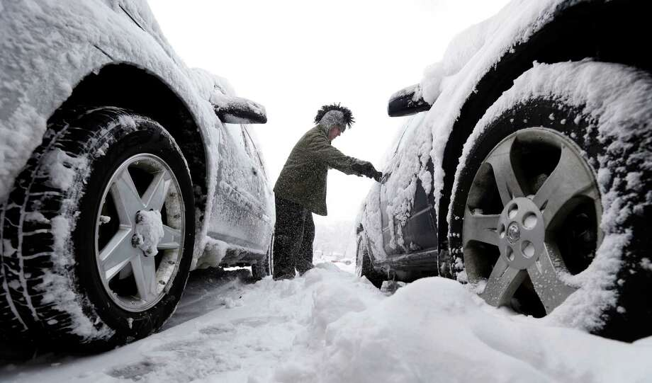 Noah Nichols, of Des Moines, Iowa, cleans snow off his car, Thursday, Dec. 20, 2012, in Des Moines, Iowa. The first widespread snowstorm of the season began a slow crawl across the Midwest on Thursday with some areas receiving as much as 15 inches of snow. Photo: Charlie Neibergall, AP / AP