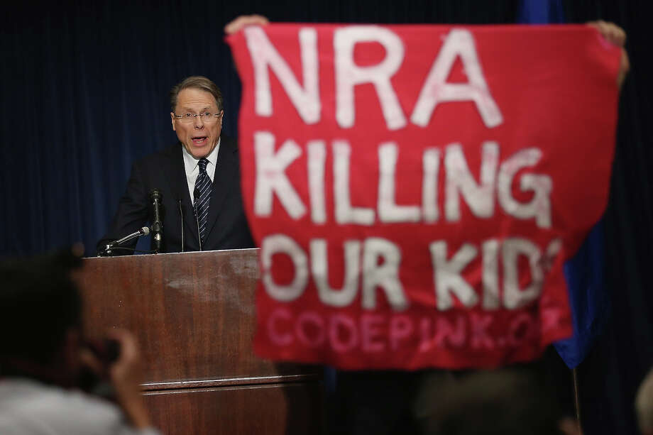 WASHINGTON, DC - DECEMBER 21:  A demonstrator from CodePink holds up a banner as National Rifle Association Executive Vice President Wayne LaPierre delivers remarks during a news conference at the Willard Hotel December 21, 2012 in Washington, DC. This is the first public appearance that leaders of the gun rights group have made since a 20-year-old man used a popular assault-style rifle to slaughter 20 school children and six adults at Sandy Hook Elementary School in Newtown, Connecticut, one week ago. Photo: Chip Somodevilla, Getty Images / 2012 Getty Images