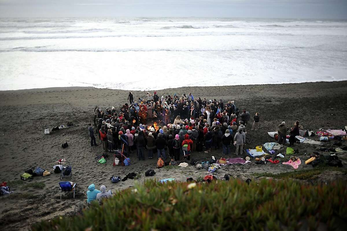 Members of the Reclaiming, a Bay Area pagan group and others gather at Ocean Beach and enjoy a fire and dip in the water to celebrate the winter solstice. San Francisco, CA Thursday December 20th, 2012.