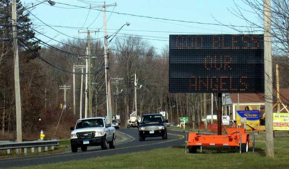 "This reader board greets visitors entering Newtown on Main Street. It switches between this message and another: ""Thanks to Our Heroes."" This sign is pictured Dec. 20, 2012, the day that four children and two adults killed had funerals in Newtown. Photo: Casey McNerthney/Hearst Newspapers"