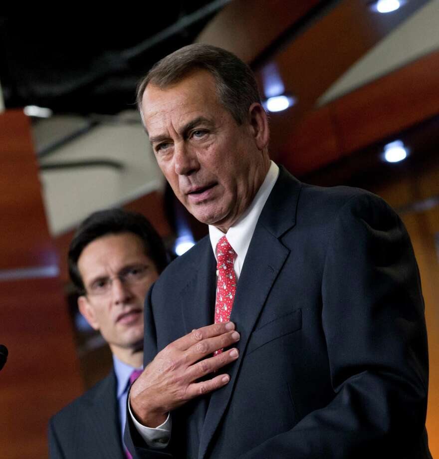 Speaker of the House John Boehner (front) speaks to reporters about the fiscal cliff  negotiations. Photo: J. Scott Applewhite, Associated Press / AP
