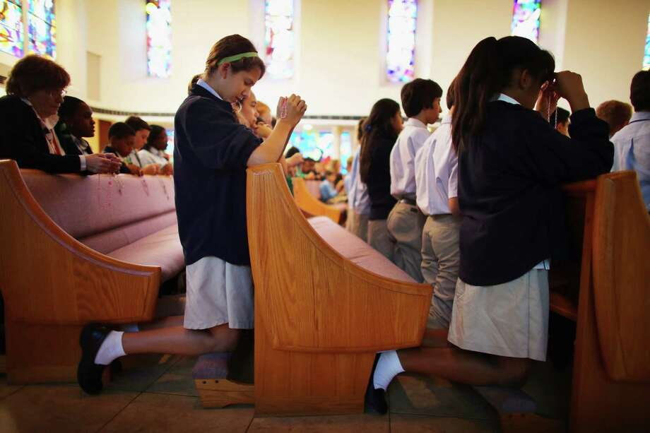 MIAMI, FL - DECEMBER 21: Nicolette Schurhoff prays during a service, at St. Rose of Lima School, for the victims of the school shooting one week ago in Newtown, Connecticut on December 21, 2012 in Miami, Florida. Across the country people marked the one week point since the shooting at Sandy Hook Elementary School in Newtown, Connecticut that killed 26 people. Photo: Joe Raedle, (Photo By Joe Raedle/Getty Images) / Getty Images