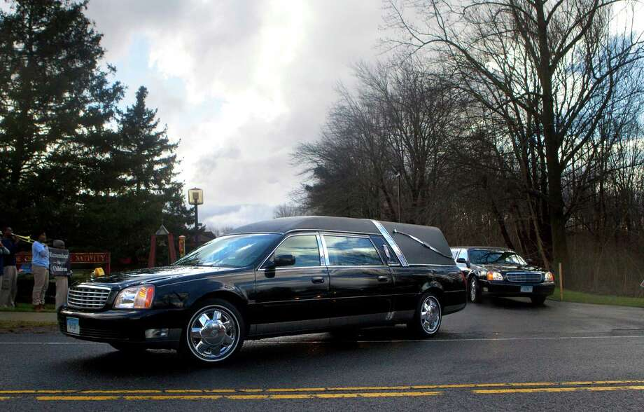The precession for Rachel Marie D'Avino drives from the Church of the Nativity in Bethlehem, Connecticut, after her funeral Friday, December 21, 2012. D'Avino was killed during a shooting at Sandy Hook Elementary School last Friday. The school was evacuated after Adam Lanza opened fire killing 26 individuals, 20 whom were children. Photo: Cody Duty, Cody Duty/Hearst Newspapers / The News-Times