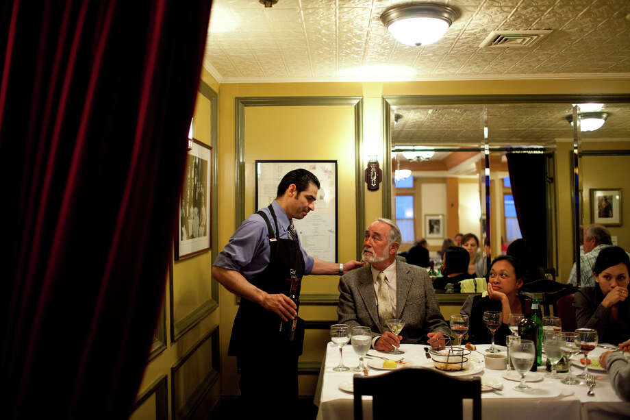 Lalo Flores, a server for 15 years, waits on patrons Gordon Bowman-Jones, whose been coming here for 30 years, and his wife Christina Photo: Jason Henry, Special To The Chronicle / ONLINE_YES