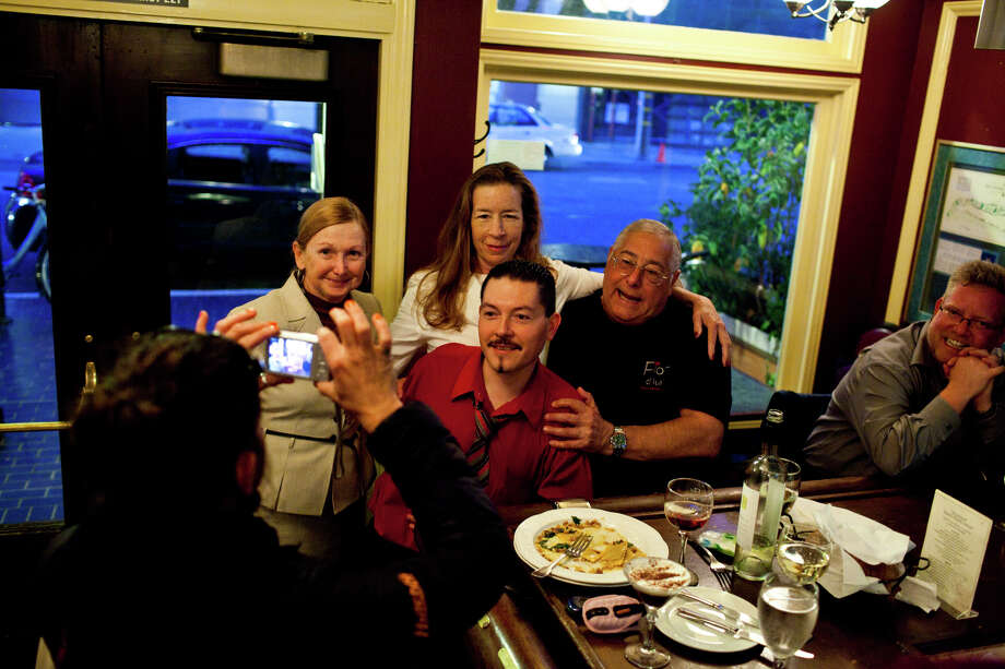 Bartender Giovanni Rivas, center, poses for a photo with patrons Photo: Jason Henry, Special To The Chronicle / ONLINE_YES