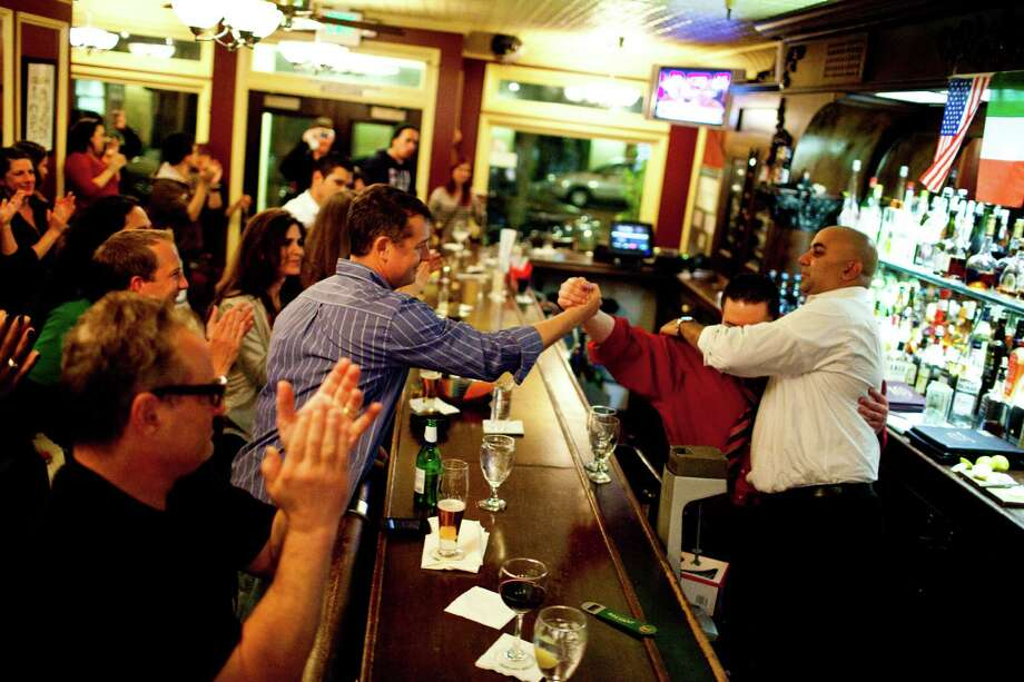Ian Larive, son of former owner Bob Larive, locks hands with bartender Giovanni Rivas after he delivered a farewell speech to patrons and staff Photo: Jason Henry, Special To The Chronicle / ONLINE_YES