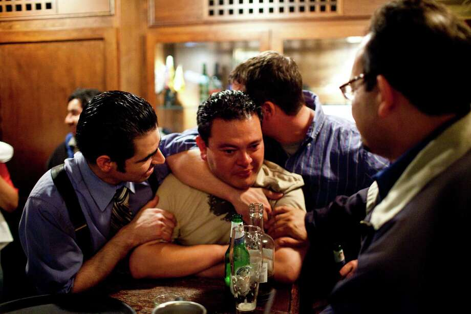 Bartender Michael Rivas is consoled by server Lalo Flores, left, and Ian Larive, son of former owner Bob Larive, Photo: Jason Henry, Special To The Chronicle / ONLINE_YES