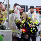 Members of the Sandy Hook Fire and Rescue Company gather for a moment of remembrance in front of a memorial to victims Friday morning as bells toll at 9:30a.m. all around the state, Dec. 21, 2012.
