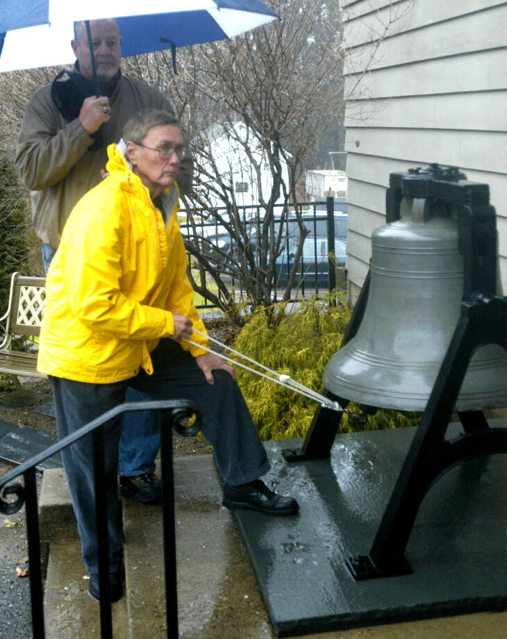 Art Putnam of the United Methodist Church of New Milford rings the church's historic bell 27 times Friday morning, Dec. 21, 2012 as the Rev. Paul Fleck, nearby, reads the names of those who died seven days earlier as the result of tragic shootings at Sandy Hook Elementary School in Newtown. Shielding Mr.Putnam from a steady rain is fellow church member Steve Kolitz. Photo: Norm Cummings