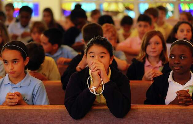 MIAMI, FL - DECEMBER 21:  Elissa Irwanto prays during a service, at St. Rose of Lima School, for the victims of  the school shooting one week ago in Newtown, Connecticut on December 21, 2012 in Miami, Florida. Across the country people marked the one week point since the shooting at Sandy Hook Elementary School in Newtown, Connecticut that killed 26 people.  (Photo by Joe Raedle/Getty Images) Photo: Joe Raedle, Getty Images / Getty Images