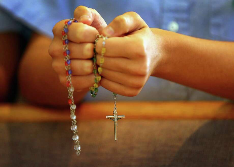 MIAMI, FL - DECEMBER 21: A child holds rosary beads as she prays during a service at St. Rose of Lima School, for the victims of  the school shooting one week ago in Newtown, Connecticut on December 21, 2012 in Miami, Florida. Across the country people marked the one week point since the shooting at Sandy Hook Elementary School in Newtown, Connecticut that killed 26 people.  (Photo by Joe Raedle/Getty Images) Photo: Joe Raedle, Getty Images / Getty Images
