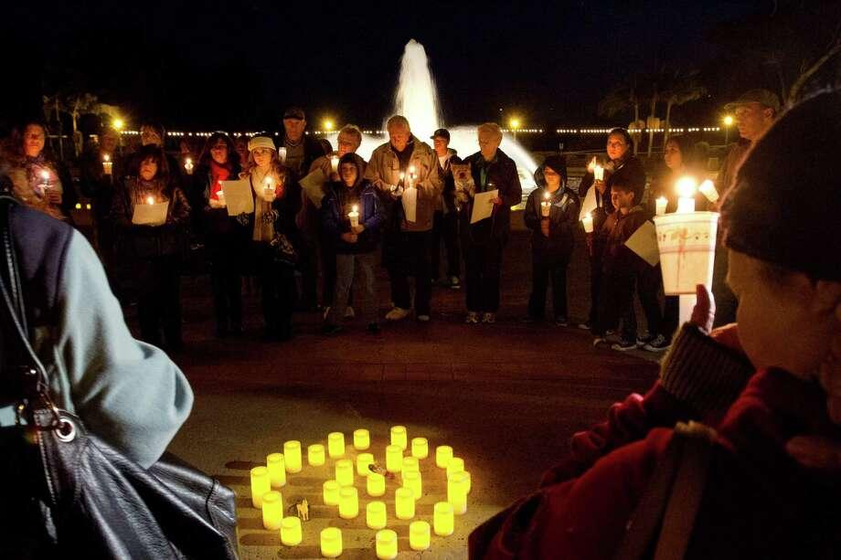People attend a candlelight vigil honoring victims of the Sandy Hook Elementary School in Connecticut at Balboa Park Thursday Dec. 20, 2012. (AP Photo/U-T San Diego, Bill Wechter Photo: Bill Wechter, Associated Press / Associated Press