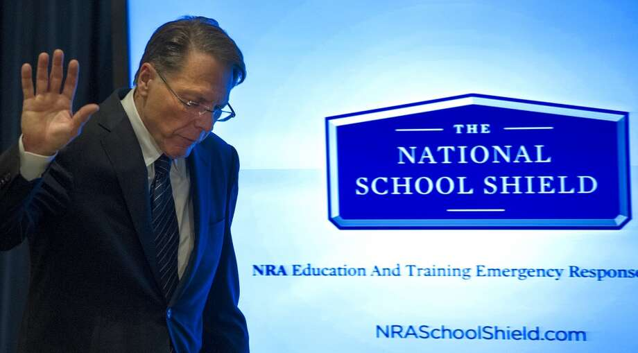 National Rifle Association (NRA) Executive Vice President Wayne LaPierre waves off questions from the media as he walks by a video screen illustratrating the NRA's proposted National School Shield,  December 21, 2012, in Washington, DC, on the one week anniversary of the Sandy Hook Elementary School shootings in Newtown, Connecticut.  The United States' most powerful pro-gun lobbying group, the National Rifle Association, called Friday for armed police or security guards to be deployed to every school in the country. The only thing that stops a bad guy with a gun is a good guy with a gun, declared LaPierre, in the group's first reaction since last week's massacre of 26 children and staff in an elementary school. (Paul J. Richards / AFP/Getty Images)