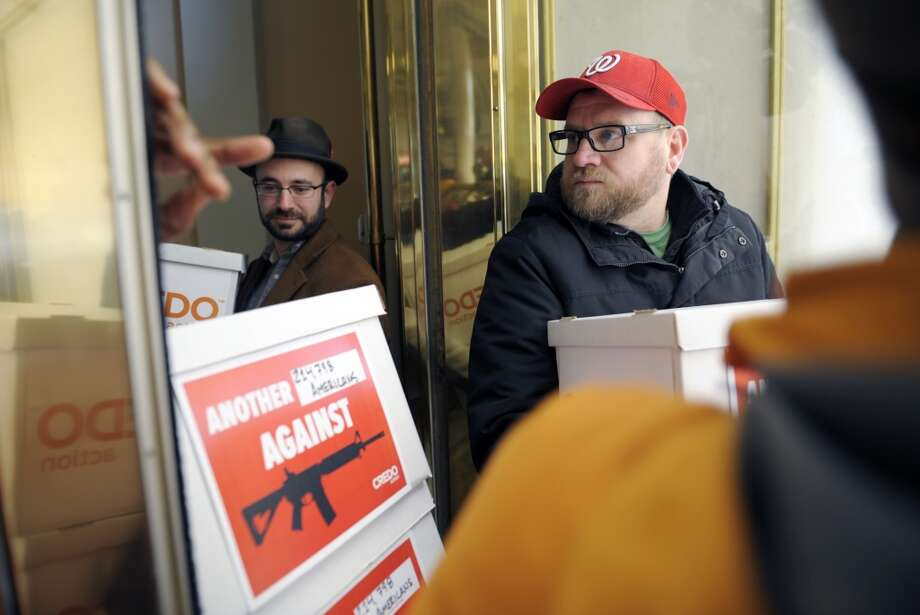 Members of Credo Mobil anti-National Rifle Association protestors are denied entrance to the front door of the Willard InterContinental Hotel after they attempted to deliver a petition to the National Rifle Association which is having a news conference in Washington, Friday, Dec. 21, 2012. The petition calls on the NRA to get out of the way of gun control legislation. (Cliff Owen / AP)