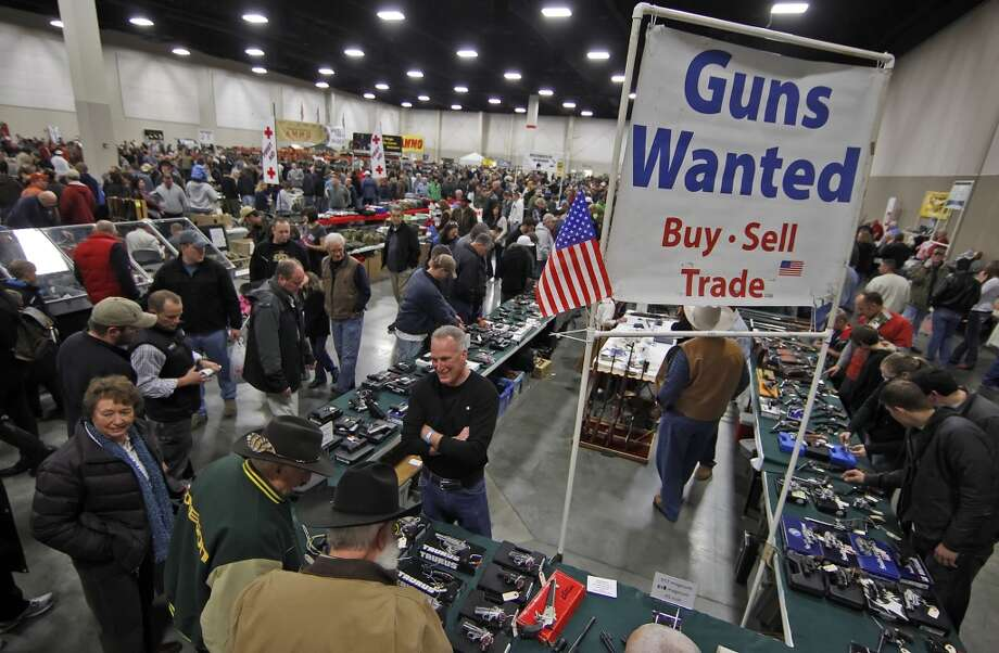 "Attendees look at guns at the Rocky Mountain Gun Show in Sandy, Utah, U.S. on Saturday, Jan. 7, 2012. The National Rifle Association called for stationing police officers in schools as the proper response to the Dec. 14, 2012 school shooting in Connecticut and blamed ""blood-soaked films"" and video games for the violence. (George Frey / Bloomberg)"