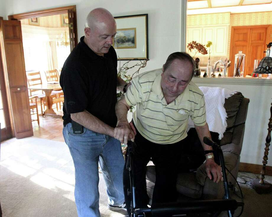 Retired Army Col. Johnny Walker helps his dad, John Walker, up from a chair. Photo: Helen L. Montoya, Staff / ©SAN ANTONIO EXPRESS-NEWS