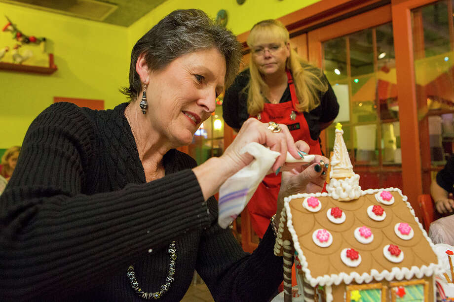 Dawn Stockton decorates a mini ice cream cone that serves as the steeple on her gingerbread church. Sharon Veatch, a workshop volunteer, observes the artist in action. Photo: Michael Miller, Freelance / © San Antonio Express-News